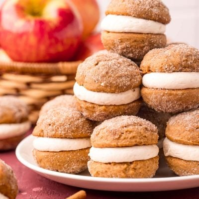 Close up photo of a stack of mini apple cider whoopie pies on a white plate with apples in the background.