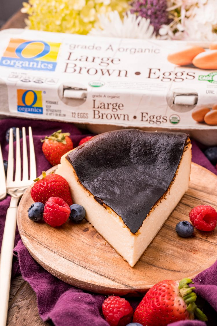 Close up photo of a slice of basque cheesecake on a wooden plate with fresh berries and gold forks. A carton of eggs is in he background.