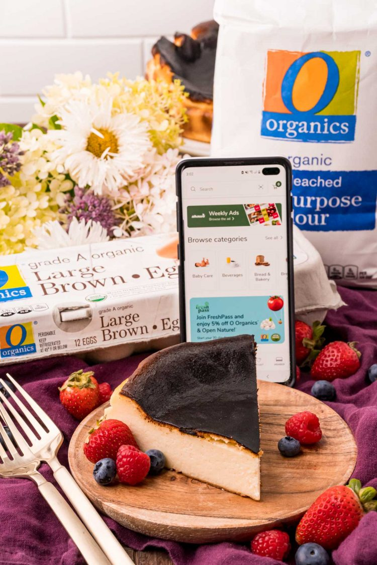 Close up photo of a slice of burnt cheesecake on a wooden plate with a carton of eggs and bag of flour in the background with a phone propped against them with the Shaw's for U app open.