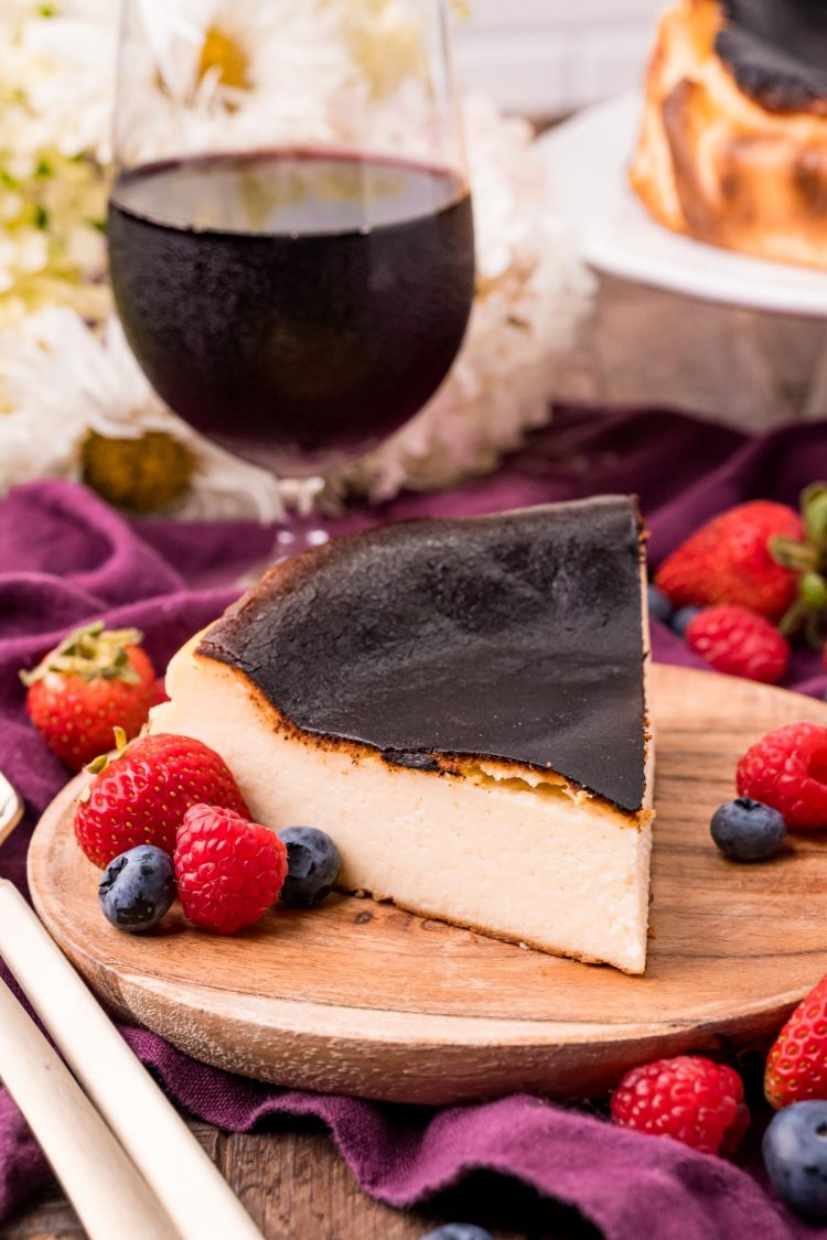 Close up photo of Basque Burnt Cheesecake on a wooden plate with fresh berries scattered around and a glass of red wine in the background.