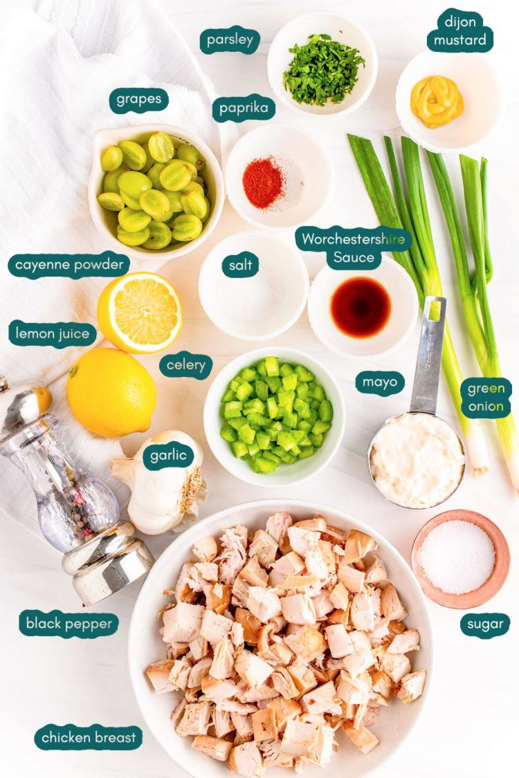 Ingredients to make chicken salad with grapes are prepped on a white countertop.