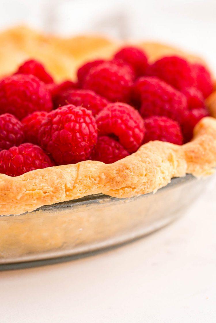 Fresh raspberries sitting in a cream cheese pie crust in a glass pie dish.
