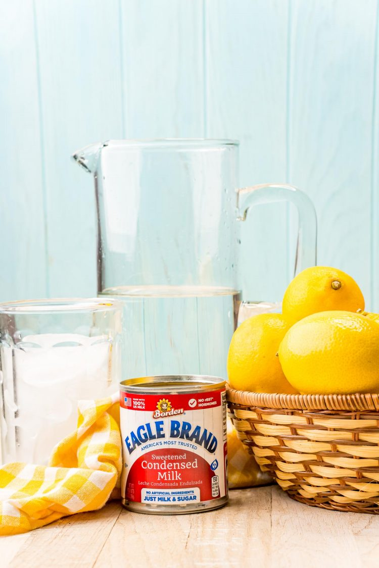 Ingredients to make creamy lemonade on a wooden counter.