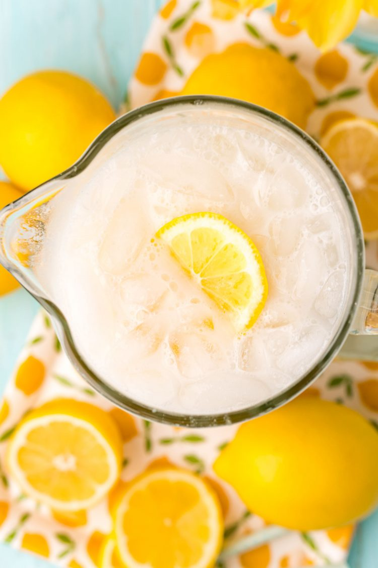 Overhead photo of a pitcher of creamy lemonade surrounded by lemons.
