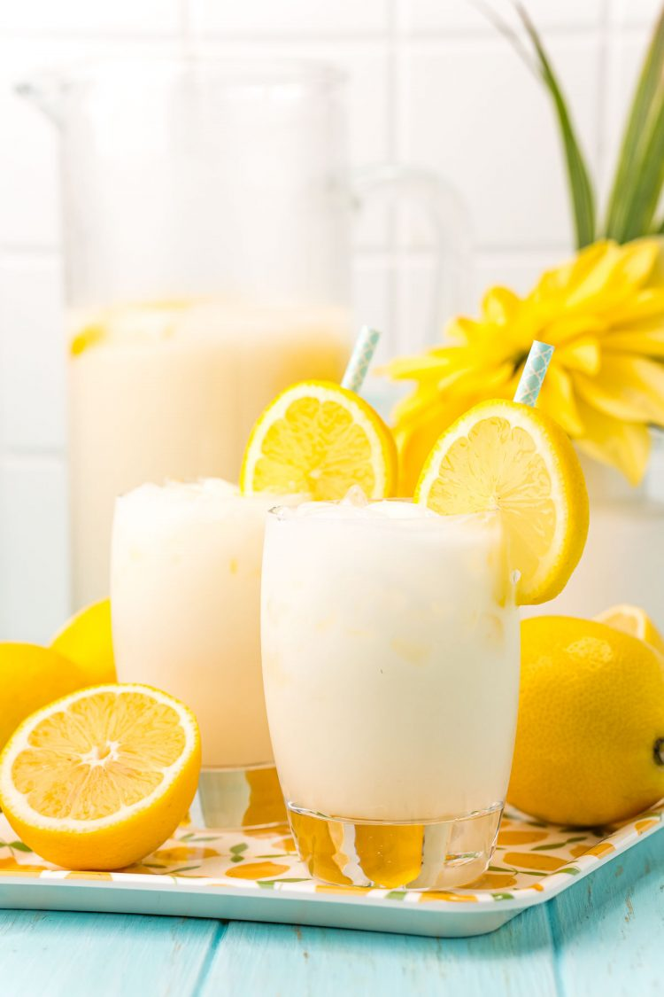 Straight on photo of two glasses of creamy lemonade on a tray with lemons and a pitcher in the background.