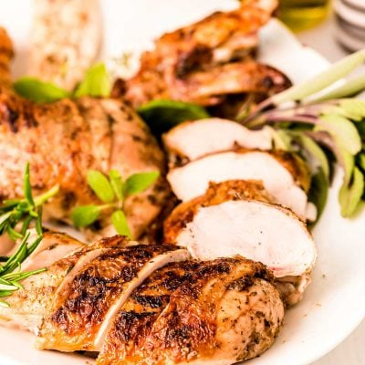 Close up photo of a white platter with a broken down grilled chicken on it.