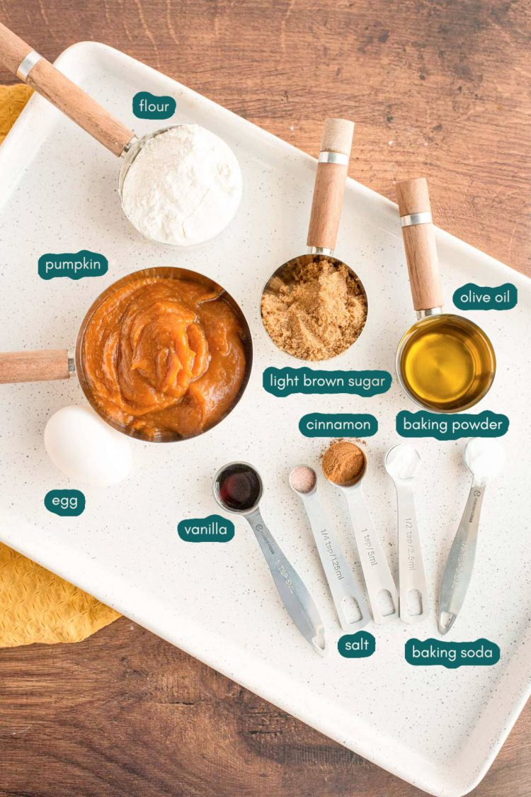 Overhead photo of ingredients to make pumpkin whoopie pies prepared on a white plate on a wooden table.
