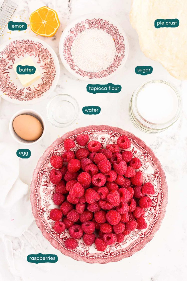 Ingredients for raspberry pie prepared on a white counter.