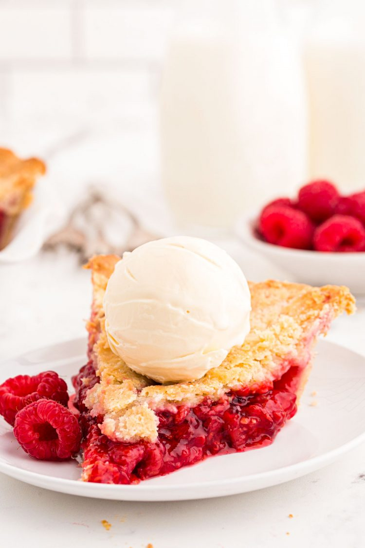 A slice of raspberry pie on a white plate with a scoop of vanilla ice cream on top.