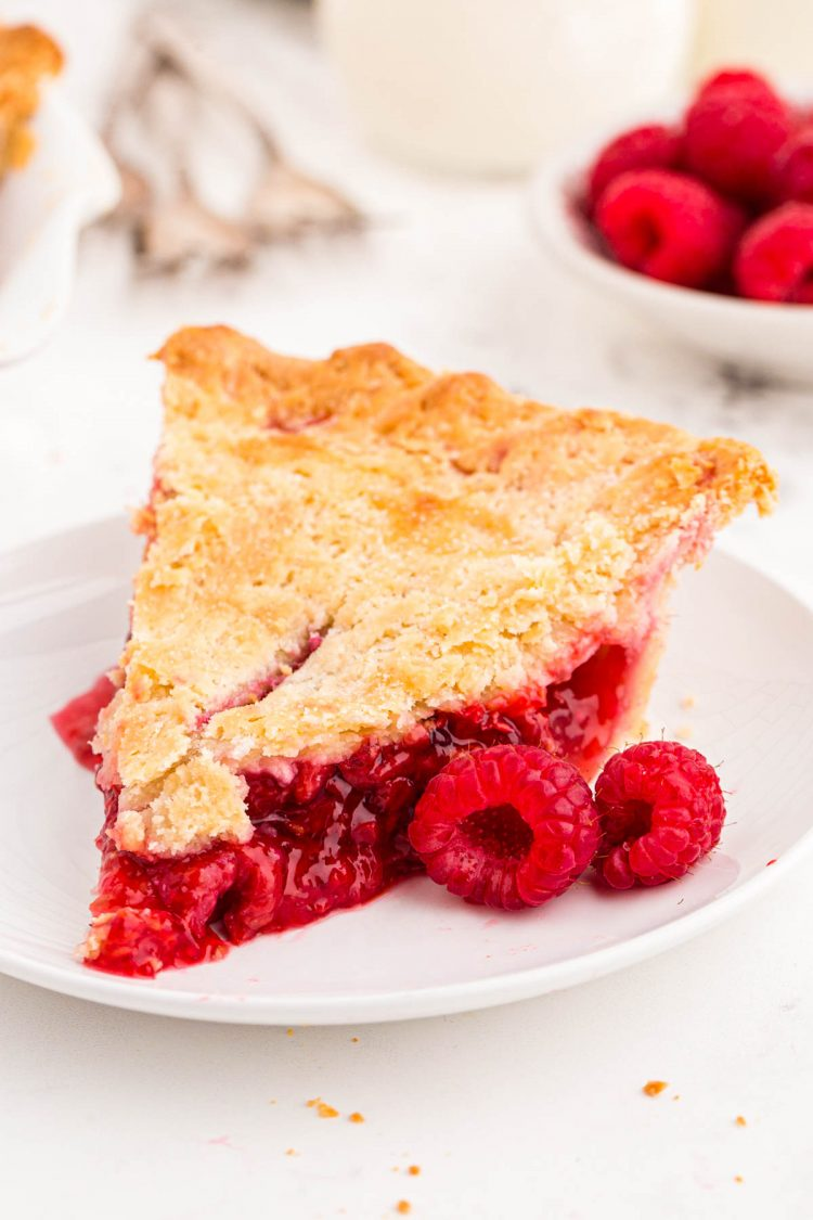 Close up photo of a slice of raspberry pie on a white plate with fresh raspberries around it.