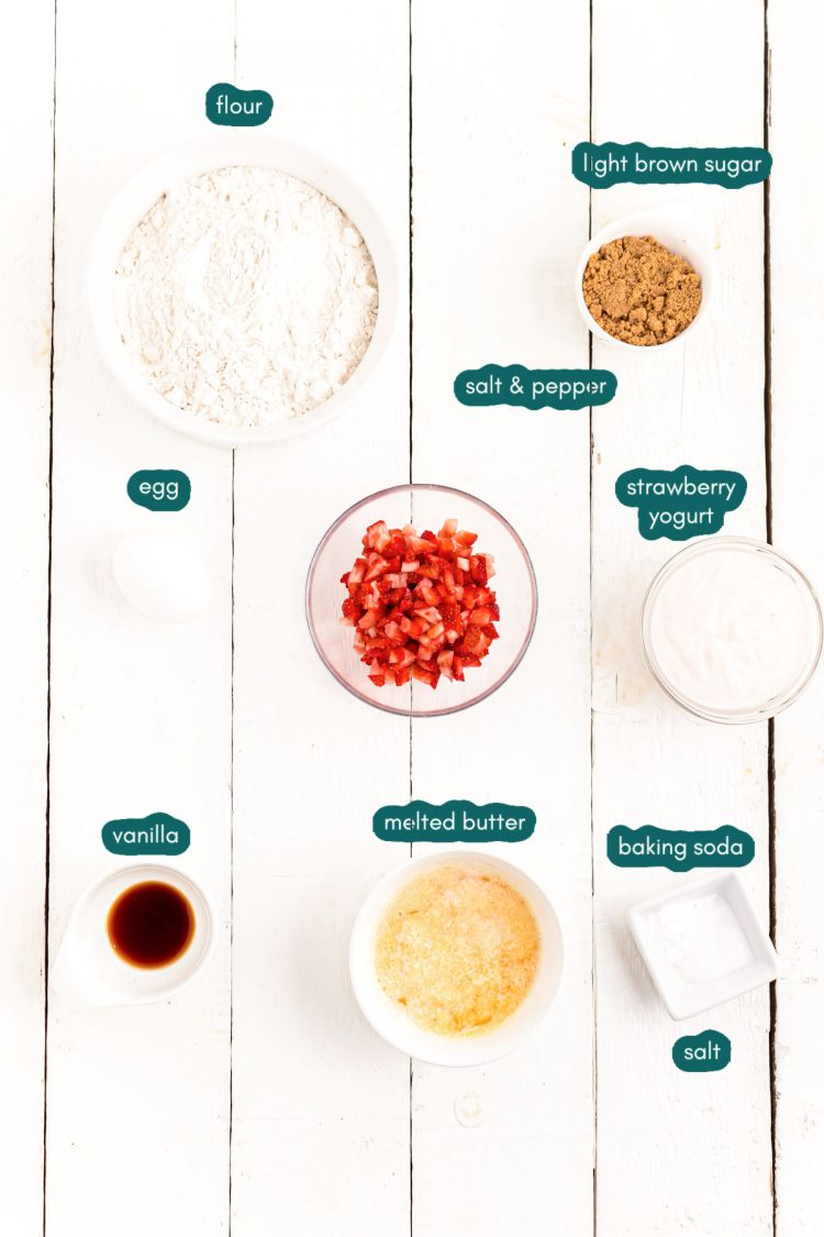 Overhead photo of ingredients to make strawberry donuts on a white wooden table.