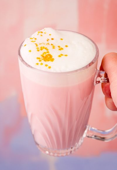 Close up photo of a woman's hand holding a mug of pink angel milk.