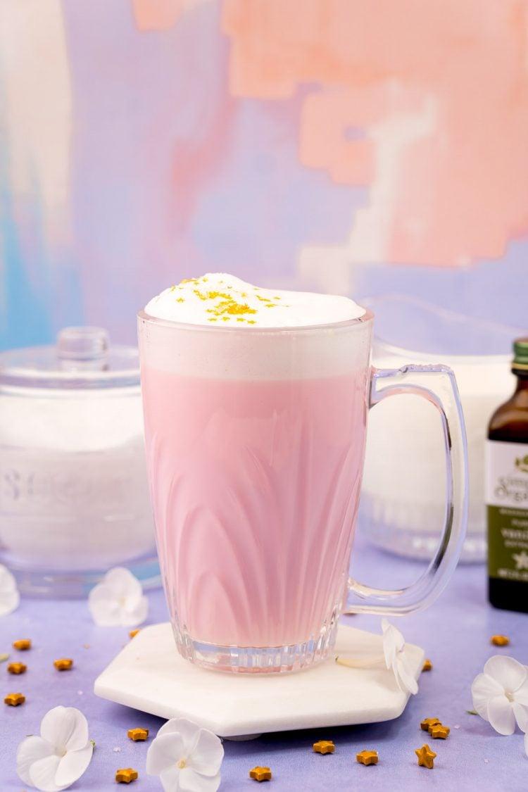 A mug of pink Angel milk on a purple surface.