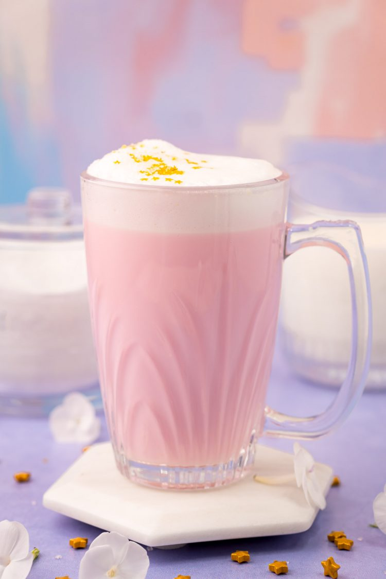 Close up photo of a mug filled with pink angel milk on a purple surface.