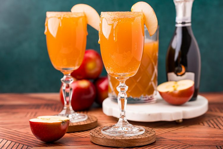 Close up photo of an apple cider mimosa in a glass garnished with an apple slice.