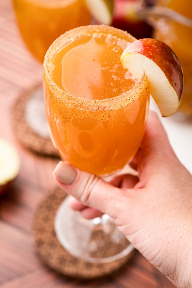A woman's hand holding an apple cider mimosa close to the camera.