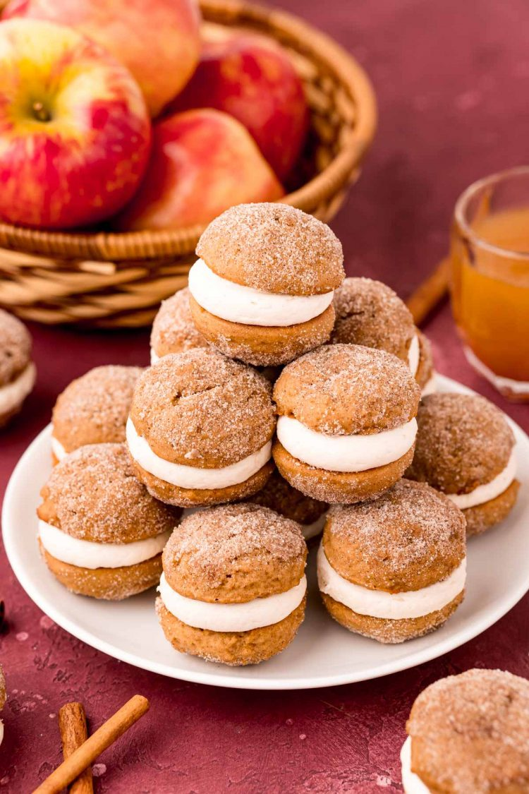 Mini apple cider whoopie pies stacked on a white plate on a maroon surface with apples in the background.