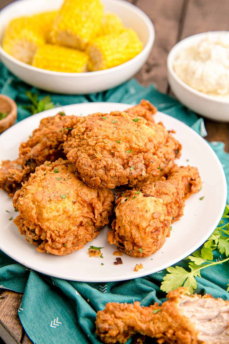 Close up photo of buttermilk fried chicken on a white plate on a teal napkin with corn in the background.