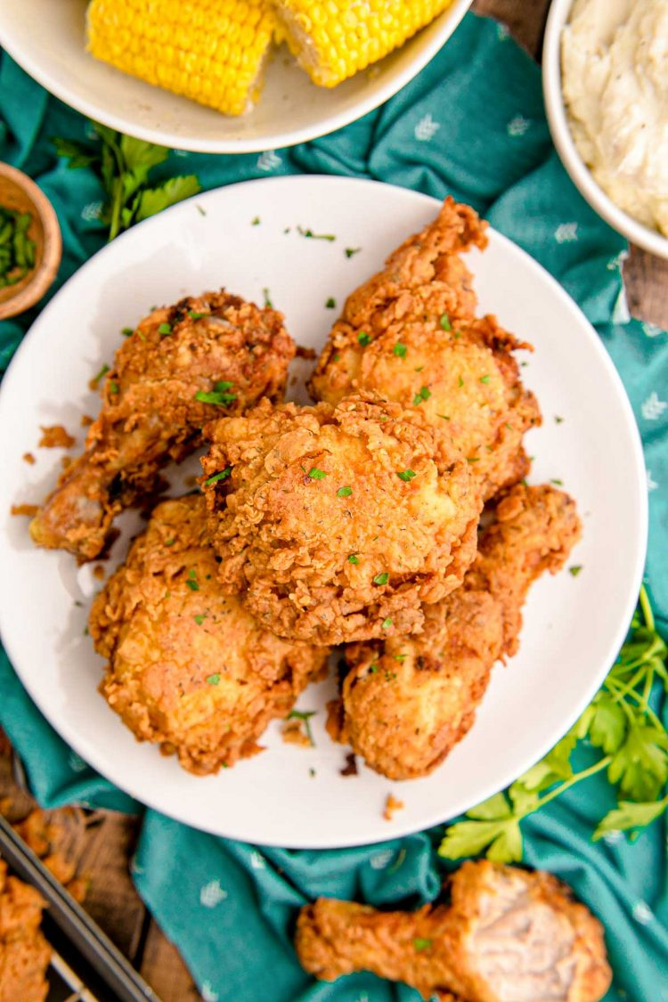 Overhead photo of fried chicken on a white plate on a teal napkin.