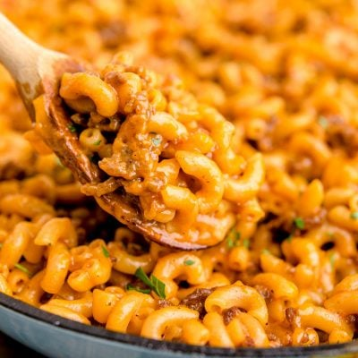 Close up photo of a wooden spoon scooping hamburger helper out of a skillet.