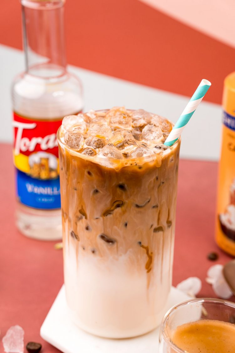 A close up photo of a glass with iced caramel macchiato in it and a bottle of caramel syrup and vanilla simple syrup in the background.
