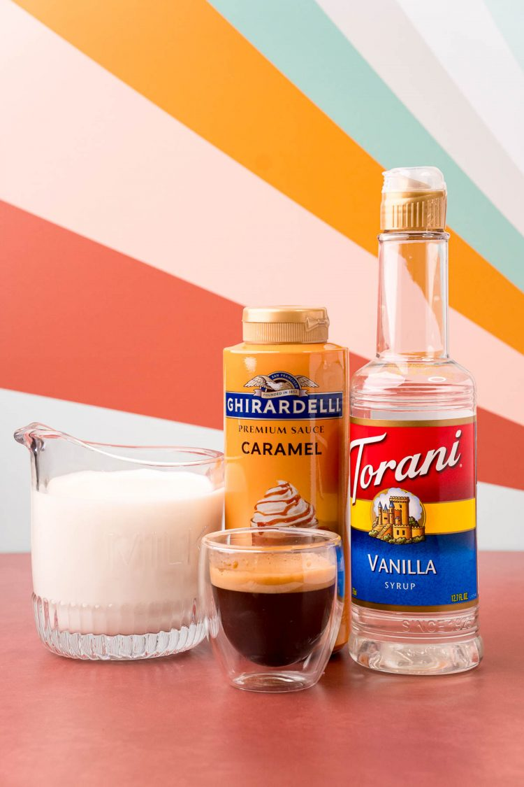 Ingredients to make an iced caramel macchiato on a red surface.