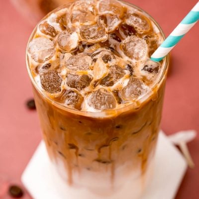Close up photo of a glass filled with an iced caramel macchiato.