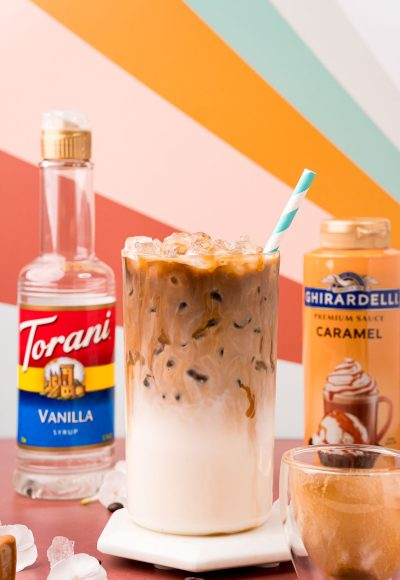 Close up photo of an iced caramel macchiato on a white marble coaster on a dark red table with caramel sauce and vanilla simple syrup bottles in the background.