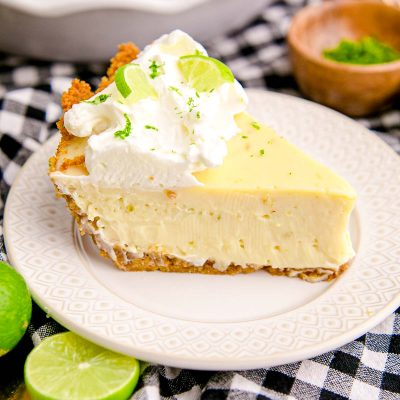 Close up photo of a slice of key lime pie on a white plate on a black and white checkered napkin.