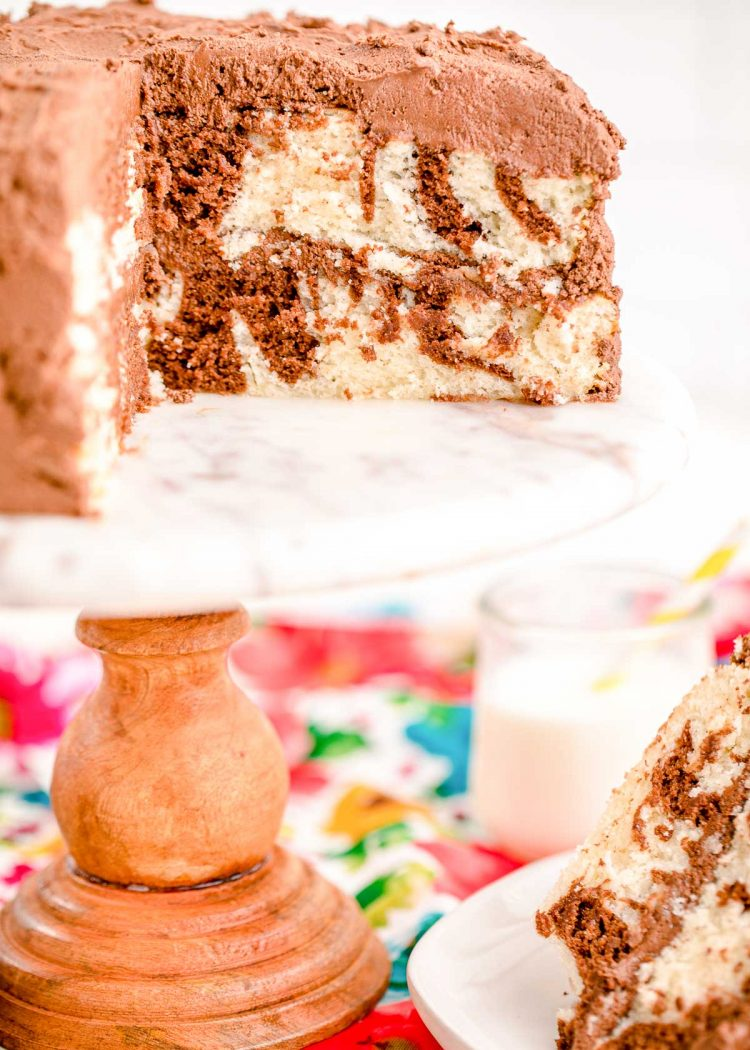 A marble cake with a slice taken out of it on a white marble cake stand.