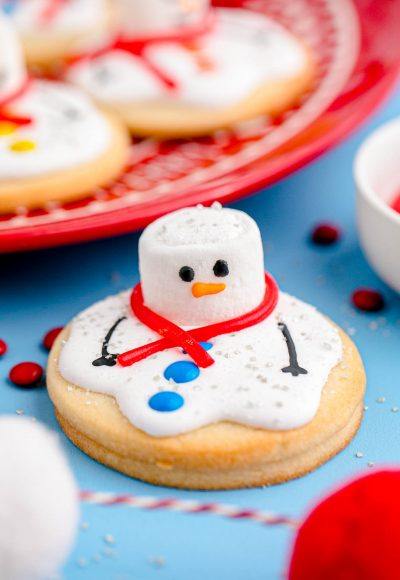 Close up photo of melted snowman cookies on a blue counter with some on a red plate in the background.