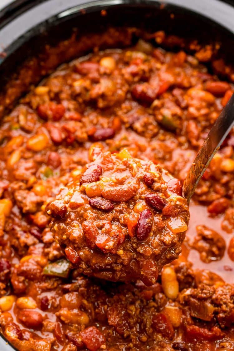 Close up photo of a ladle scooping chili out of a crockpot.