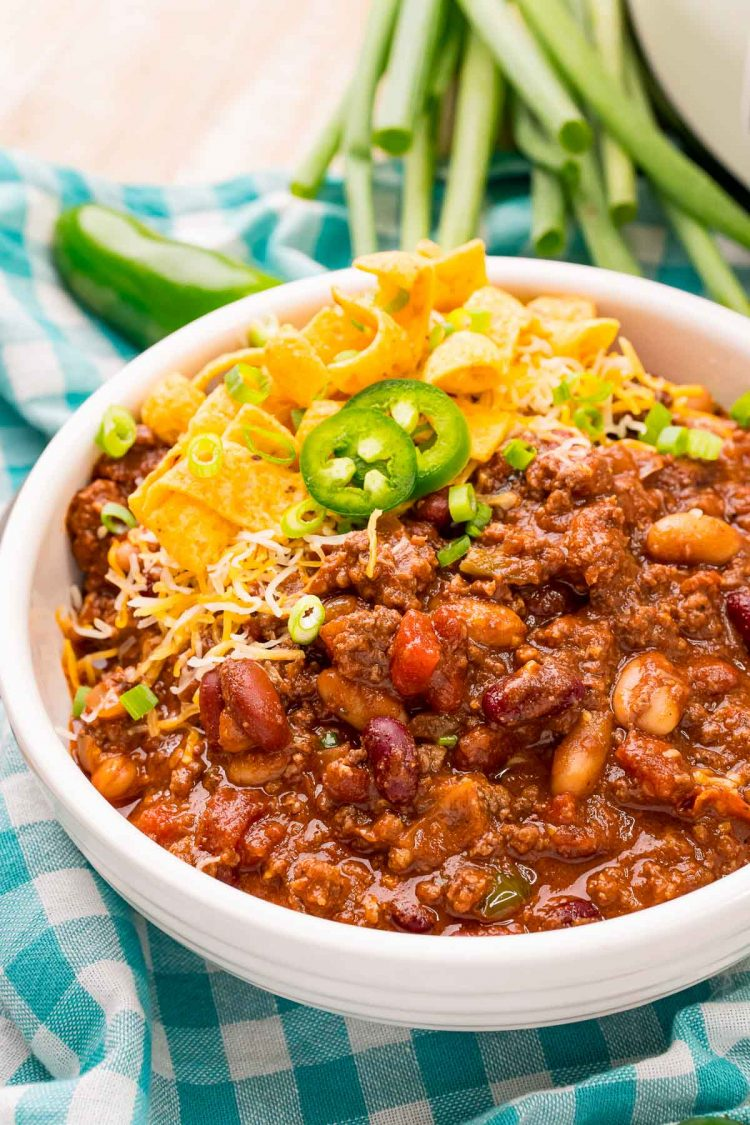 Close up photo of chili in a white bowl on a gigham napkin with peppers in the background.