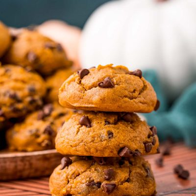 A stack of three pumpkin chocolate chip cookies on a table with a plate of more cookies in the background.