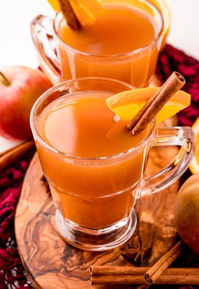 Close up photo of two mugs of mulled cider on a wooden cutting board garnished with a cinnamon stick and orange slice.