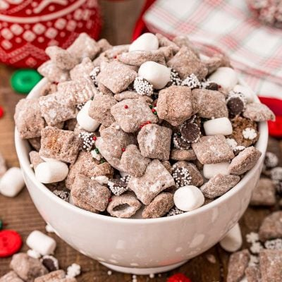 A white bowl filled with hot chocolate muddy buddies on a wooden table with muddy buddies and holiday decorations scattered around.