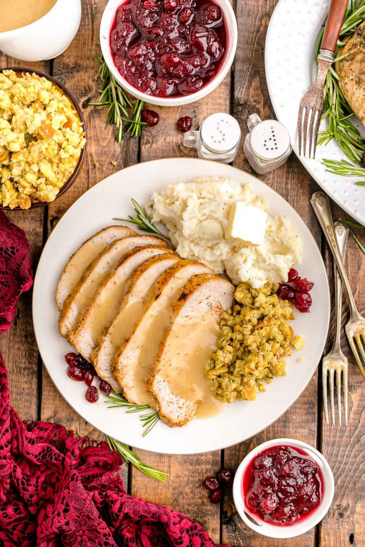 Overhead photo of a plate with a Thanksgiving dinner on it on a wooden table with side dishes and napkins around it.