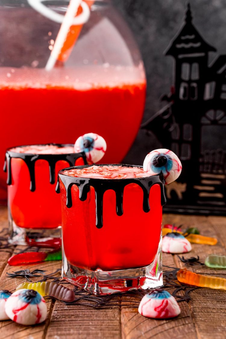 Photo of two glasses with Werewolf Halloween punch in them on a wooden table surrounded but gummy worms and eyeball gummies with a large punch bowl in the background.