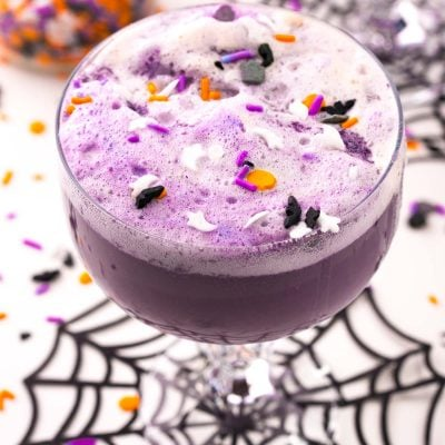 Close up photo of a stemmed glass filled with witch's brew halloween punch on a spider web coaster.