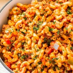 American Chop Suey is a delicious and easy dinner recipe made with ground beef, tomato, onion, green pepper, macaroni, and spices. Pure comfort food made on the stovetop in just 30 minutes and makes a great weeknight dinner!